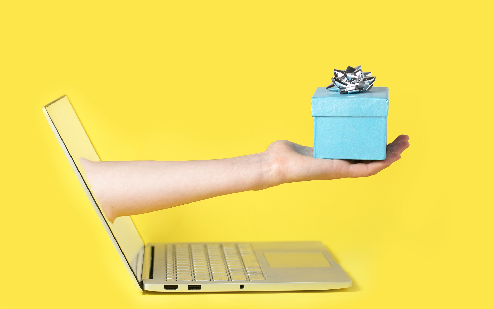 A hand coming out of computer screen and presenting a wrapped gift