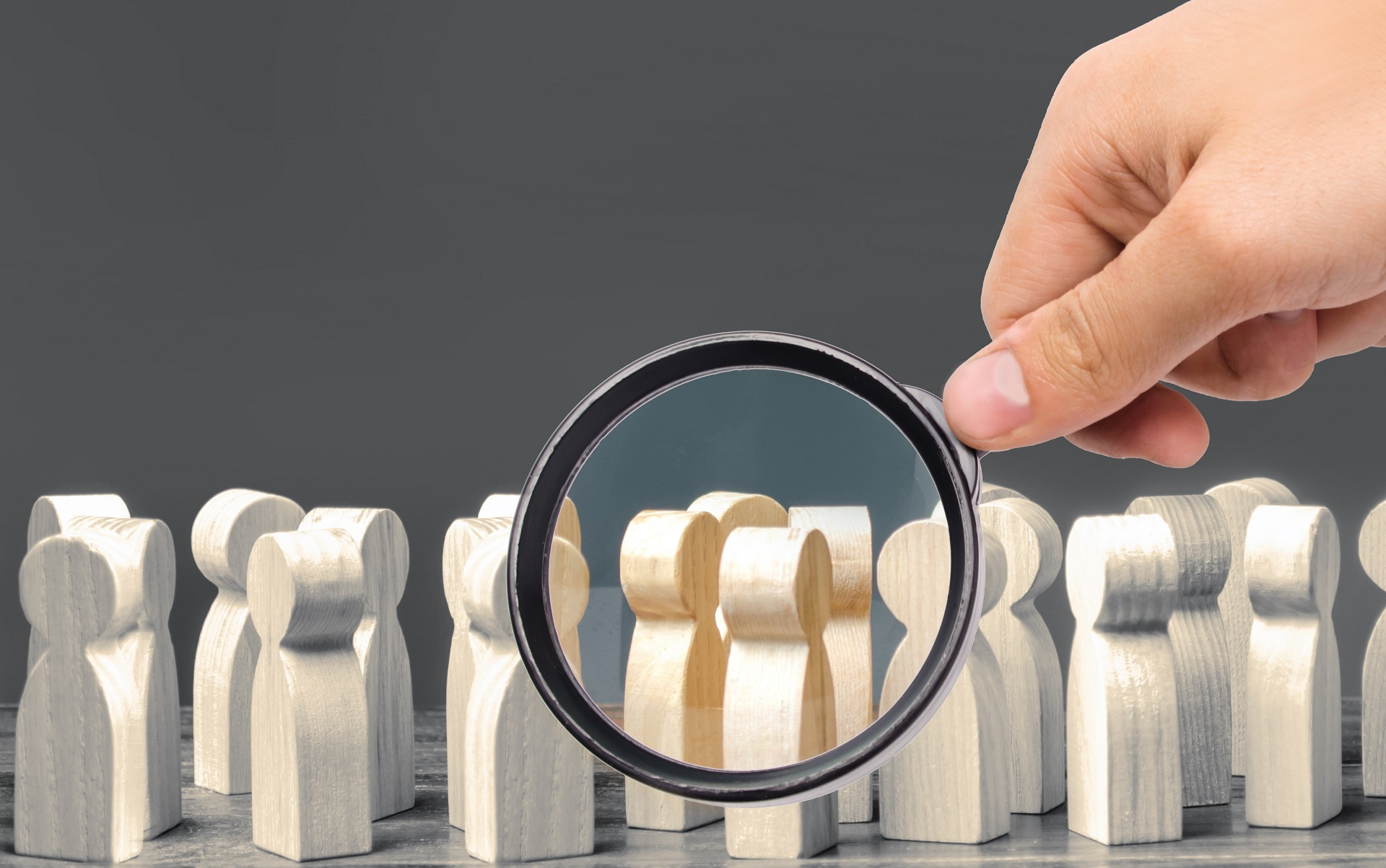 A magnifying glass looks at a crowd of wooden figures (as symbolic representation of segmentation in email marketing)