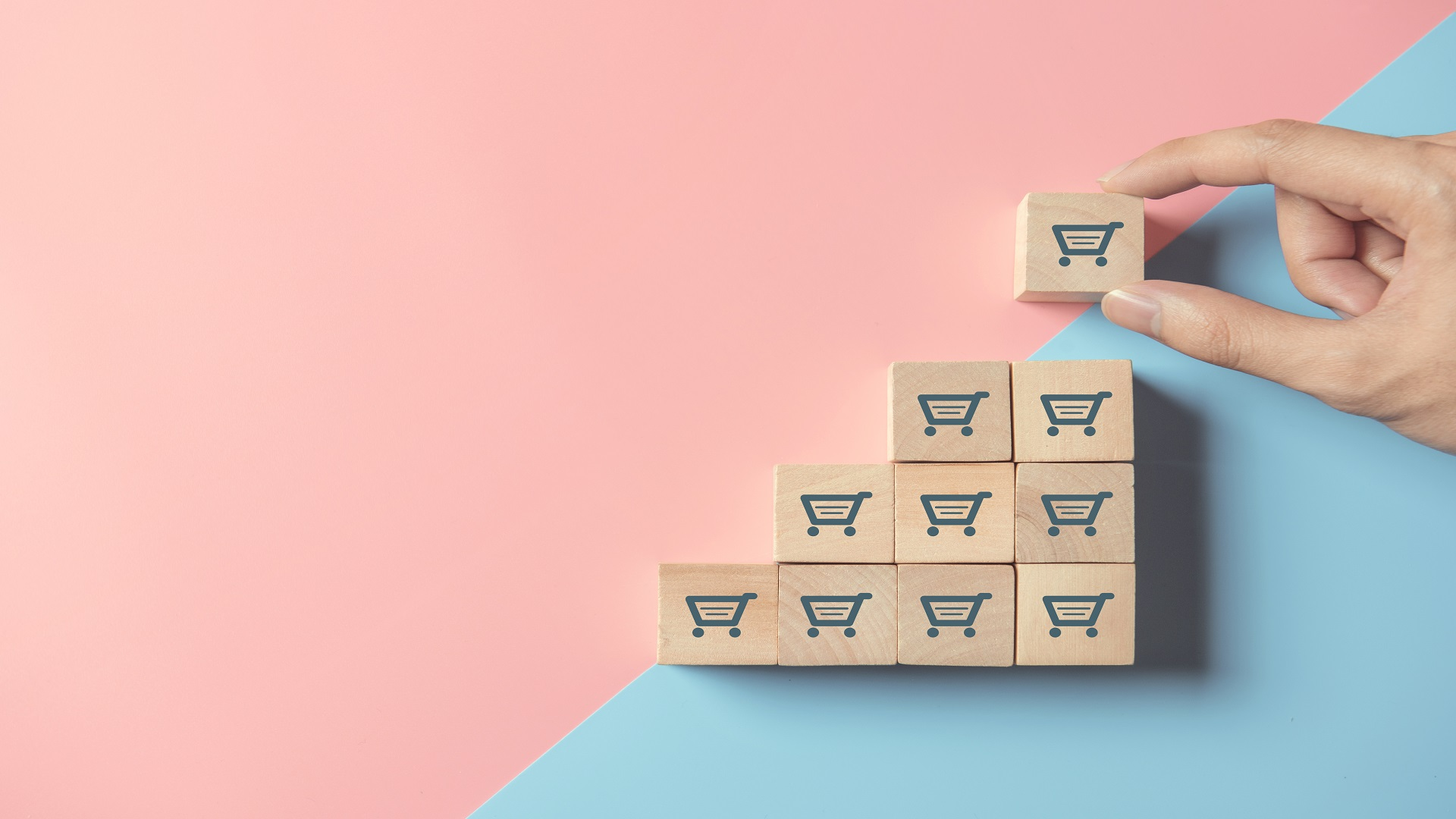Person stacking blocks with a cart symbol - symbolizes how to grow your SaaS using automation
