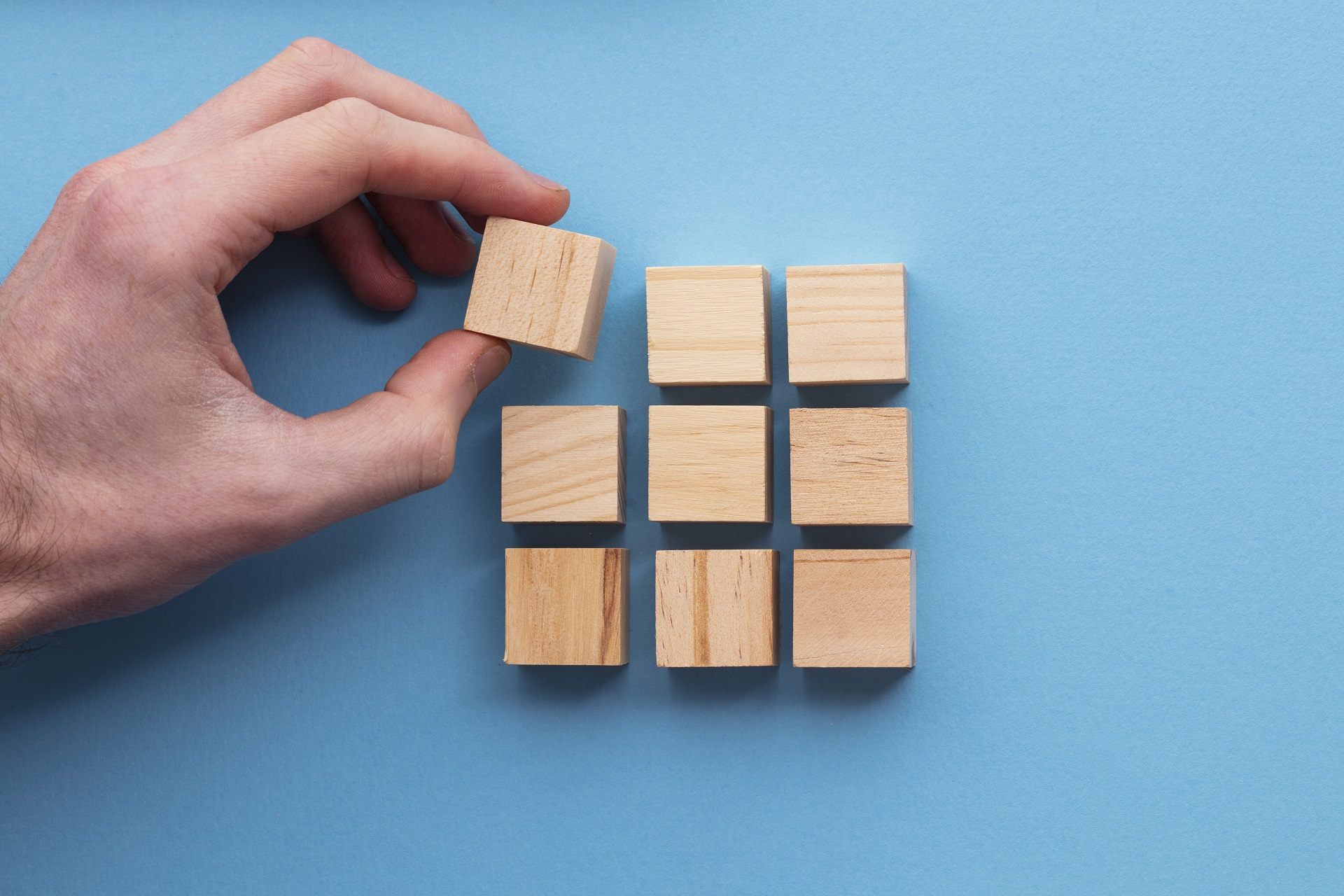 Hand placing wooden blocks in a pattern, symbolizing building something