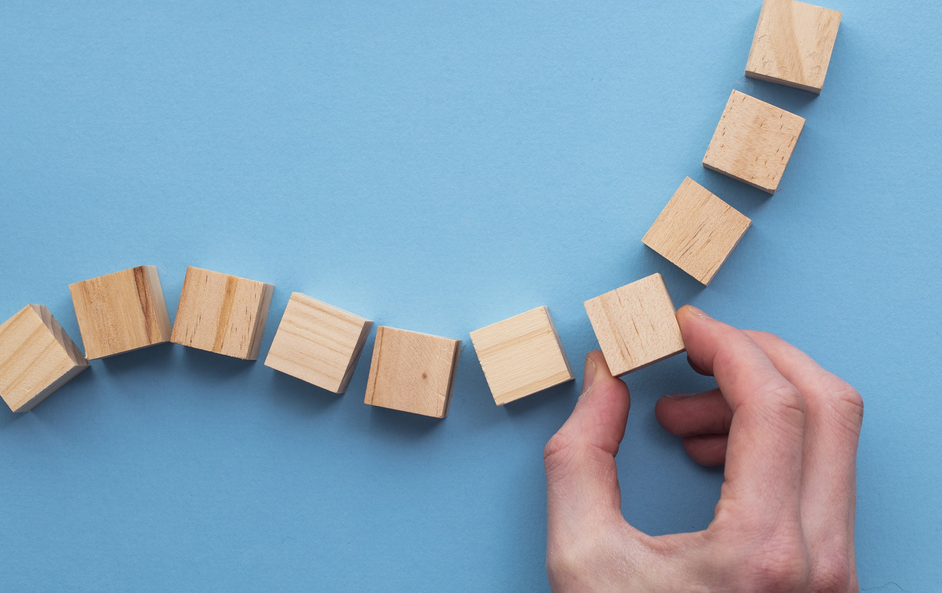 Hand placing wooden blocks in a sequence, representing the customer journey experience